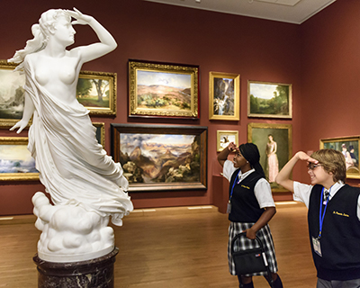Two students demonstrate a statue's pose at the Philadelphia Museum of Art